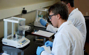 Patrick weighing samples for an analytical balance.